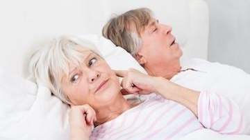 Old age couple sleeping on bed