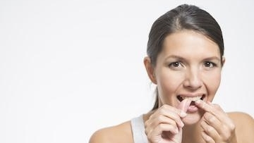Woman flossing her teeth with dental floss