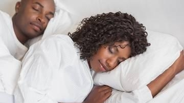 African couple sleeping on bed